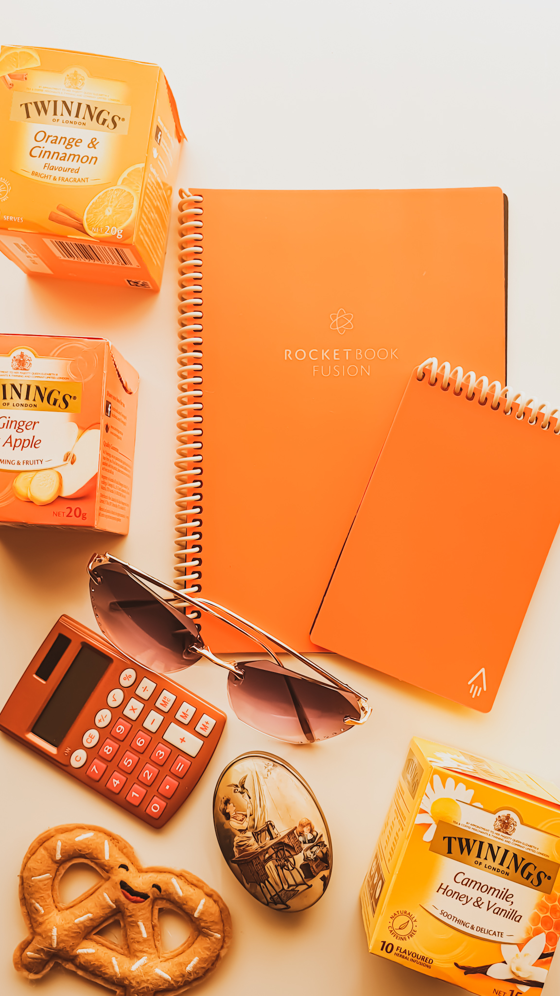 Orange spiral bound rocketbook notebook surrounded by bits and bobs like a happy fabric pretzel and tea boxes.